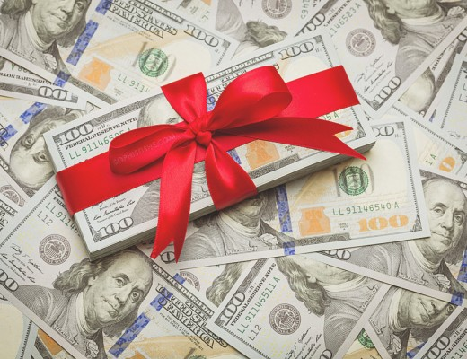 Stack of Newly Designed U.S. One Hundred Dollar Bills Gift Wrapped in Red Bow.