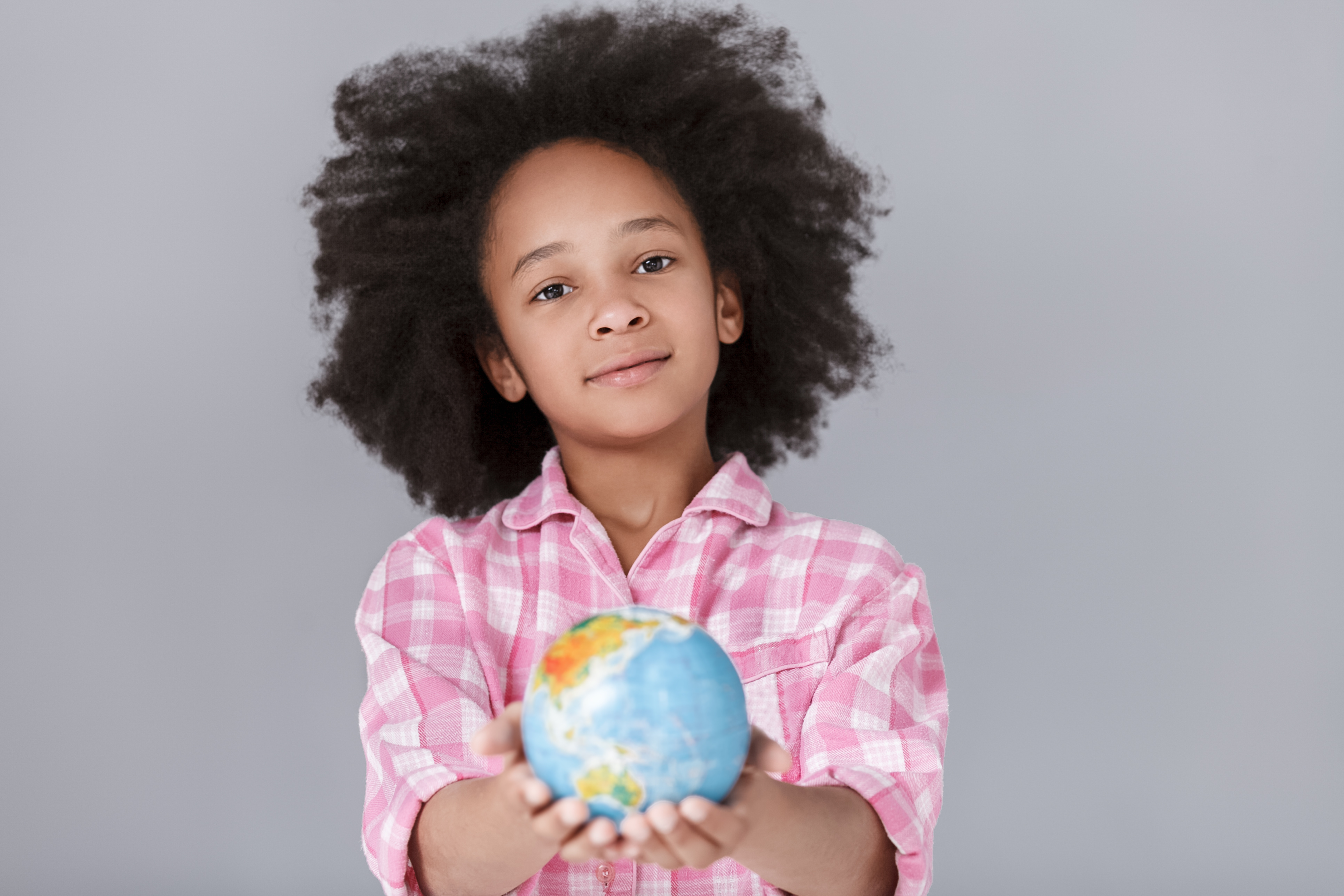 World in my hands! Cheerful little mulatto girl holding a globe while standing against grey background